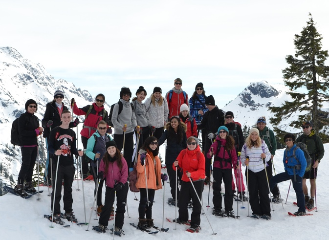 students wearing snowshoe gear pose on a snowy mountainside
